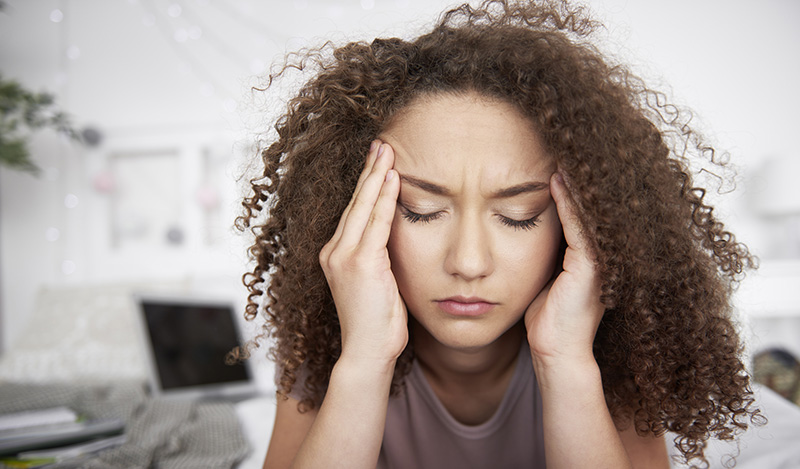 Young woman has a bad headache and is stressed out. cbd for mental health, does it work? cbd oil dose for mental health.